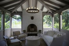 christainmiami: outdoor living area  fireplace, white round cocktail table,  white tufted sofa, chairs ...