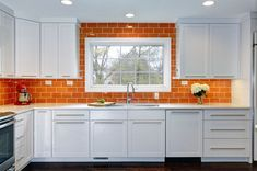 Orange subway tiles give this kitchen some fresh squeezed brilliance. #housetrends