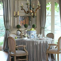Pamela used olive branches as tie backs in the dining room and covered the table with a linen check.   This chandelier is fabulous and I really like the simple rosemary wreaths around each candle.