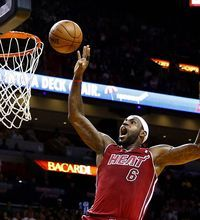 Dec 16, 2013; Miami, FL, USA;  Miami Heat small forward LeBron James (6) dunks the ball as Utah Jazz point guard Trey Burke (3)looks on in