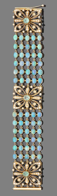An opal, demantoid garnet and half pearl braclet.  The bracelet designed as five rows of collet-set cabochon opals, between square openwork panels of floral design, each set throughout with half-pearls and a central oval-cut demantoid garnet
