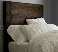 clean white bedding resting on a rustic head board w/ grey walls- love it!