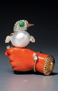 CARTIER brooch set with emerald, diamond, coral and pearl. The coral hand is holding a little bird with a pearl body. 1930