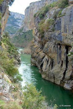 La Foz de Lumbier, Navarra - Spain Es una estrecha garganta labrada por el río Irati declarada reserva natural. Un paisaje agreste en el que podemos ver buitres leonados sobrevolando el acantilado; bravos escarpes donde nidifican las aves; un río de limpias y frescas aguas que talla en las rocas estrechos y caprichosos pasos; los restos de un puente que, según cuenta la leyenda, fue construido con ayuda del diablo; dos túneles que antaño atravesó el primer tren eléctrico de España. Places In Spain, Places To See, Places Around The World, Around The Worlds, Mountain Waterfall, Basque Country, Amazing Nature, The Good Place, Cool Pictures