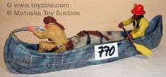 Vintage toy indians in canoe