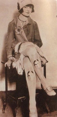 Miss Kitty Lee, society girl of Baltimore, with a portrait of her boyfriend printed onto her stockings. c. 1920s