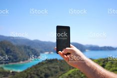 A Hand holds up a Mobile Phone to take a photo of the view. Abel Tasman National Park, Kiwiana, Landscape Photos, Image Now, How To Take Photos, National Parks, Royalty Free Stock Photos, Lifestyle, Phone
