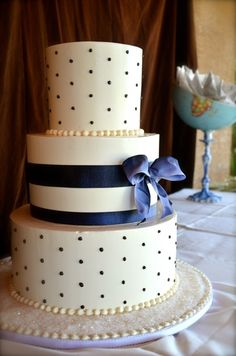 Such a gorgeous wedding cake, ivory colored icing, navy blue ribbon, with navy pearl sized dots. Traditional tiers. Very romantic! I just wish that instead of ivory it was white. And I wish that the blue had a little bit of a silvery tint in it.