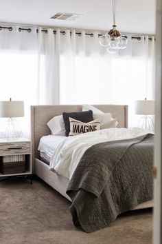 Bed in front of window with curtain back drop // airy light bedroom