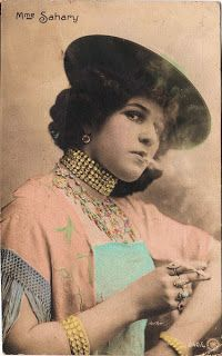 Click above to enlarge imageHere's a sassy Victorian lady smoking a cigarette! This French woman is wearing a Bohemian looking edwardian dress and is all decked out in her best jewels, including multiple rings, a rhinestone choker and matching bracelets. Edwardian Dress, Edwardian Fashion, Smoking Ladies, Graphics Fairy, Retro Humor, Victorian Women, Female Images, Costume Design, Looking For Women