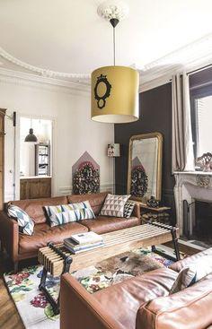 CôtéMaison   A family house near Paris   love the leather sofas, dark grey wall...