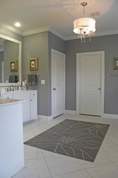 A grey bathroom with a splashes of white lighten the room and create a bright space