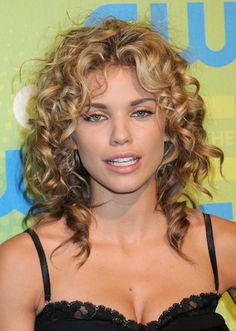 curly hair style with long, extremely curly hair in a down style with a fringe, or bangs.