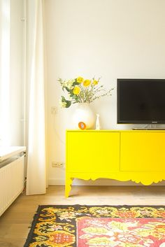 Yellow IKEA Trollsta sideboard. I like the rug and the colors of this room.