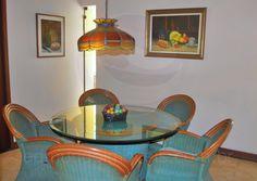 Na área íntima, uma mesa com tampo de vidro serve como apoio para as refeições noturnas.
