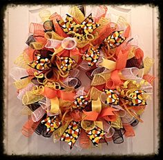 Halloween Candy Corn Deco Mesh Wreath/Candy by CKDazzlingDesignIt is made with orange, yellow, white and black deco mesh; silky orange and yellow ribbons and candy corn ribbons; Orange flex tubing and glittered yellow springs