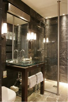 The ensuite bathroom clad in riven slate with close fitted halogen downlights to enhance the surface texture.