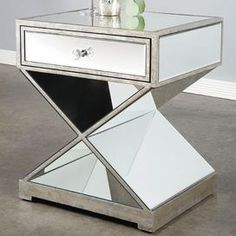 Mirrored side table with open X-base. Product: Side table    Construction Material: Mirrored glass and wood    Color: Silver       Features: One drawer    Dimensions: 23 H x 20 W x 17 D