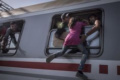 Refugees helped a migrant child board the train to Zagreb, Croatia, from the Tovarnik station near the Serbian border with Croatia. NYT