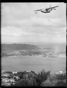 TEAL (Tasman Empire Airlines Ltd) Solent flying boat Ararangi above Evans Bay during familiarisation flight. The Wellington Gas Company plant and Lyall Bay are in the background. Photographed by an Evening Post staff photographer on the of September Auckland New Zealand, Air New Zealand, Short Sunderland, Plane Icon, Wellington New Zealand, Float Plane, Flying Boat, Aircraft Photos, Evans