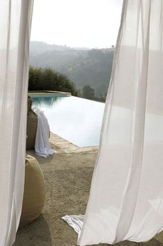 creamy stone and white muslin curtains leading to an infinity pool - Room Seventeen: Summer
