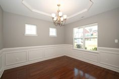 Formal dining room with dark hardwood flooring, dove gray walls, clerestory windows, wainscoting, and tray ceiling.