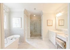 All-white bathroom features pedestal bathtub, patterned tile and plain white walls, glass entry shower and rolled back makeup chair.