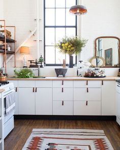 Beyond gleaming white tile, there's nothing Pinterest lovers fiend after more than a whitewashed brick wall, as seen in this upper-cabinet-free industrially bohemian kitchen.