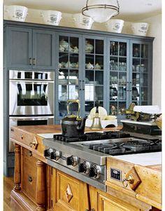 white ceramic english milk pails on top of blue kitchen cabinet