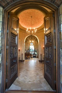 Front Entrance: Mediterranean, Tuscan, European Architecture, entry foyer, high ceiling with a terracotta mosaic, wood double doors, arch double door, venetian plaster, arched walls, chandeliers, stone floor.
