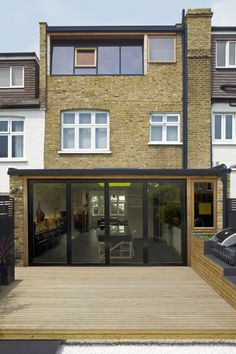 A characterful family house in London has been modernised and extended. The rear façade architecture has been re-modelled with laminated timber and black metal features, inserted into the existing bricks. Cleverly positioned skylights and windows,. Laminate Flooring In Kitchen, Dormer Windows, London House, Diy Pergola, Pergola Carport, Pergola Ideas, Patio Ideas, House Extensions, Brickwork