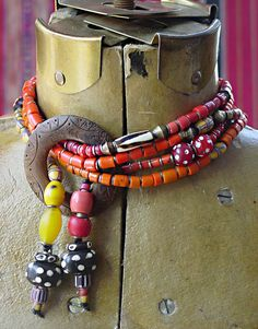 by Helena Nelson-Reed | Necklace combining a collection of antique African Trade beads, Naga tile beads spaced with slivers of antique bronze, from Borneo, Sherpa coral from Tibet, contemporary batik bone beads from Africa.