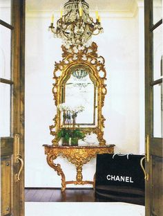 Some favorite bits of gilt…  18th century Venetian mirror…  2oth century gilded console, bronze and crystal chandelier…  That Chanel shopping bag is inspired…and the offset green  potted white orchids…