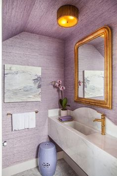 Charming purple powder room is clad in purple grasscloth wallpaper illuminated by a gold bamboo flush mount fixed to a wallpapered ceiling.