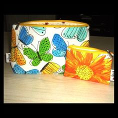 """Clinique NWT Spring 2016 Matching Cosmetic Bag Duo BRAND NEW Clinique Cosmetic Bag Duo- PERFECT for upcoming Spring/Summer seasons! The larger bag is adorned by gorgeous blue flowers and beautiful, bright yellow butterflies. Measures 10""""(L) x 6""""(H); Fabric Lining with ADORABLE ladybug pattern on the inside. The smaller bag is adorned with stunning, bold sunflowers in sumptuous orange and yellow hues. Matching ladybug-sprinkled lining. Measures 5""""(L) x 3 1/2""""(H). Both bags have Clinique metal…"""