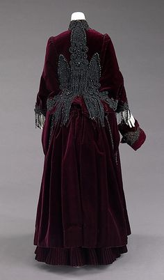 Jet-beaded burgundy silk velvet carriage dress (back, with dolman and muff), by Mme. Uoll Gross, American, ca. 1885. This dress was designed to be worn in an open top carriage which, at the time, was a social event and everyone had to dress the part. Part of ensemble with matching dolman coat, small muff, and hat with ostrich feathers and geometric jet decoration.