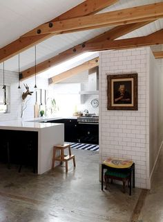 Beautiful open floor plan kitchen with white subway tiles and exposed wood beams on the slanted ceiling.