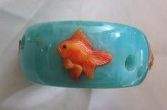 Tangerine and turquoise, like this  goldfish inlaid into turquoise bakelite.