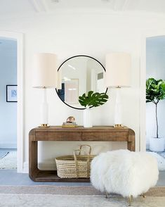 Entry styling. Rustic wood console in a modern shape, round mirror, basket.