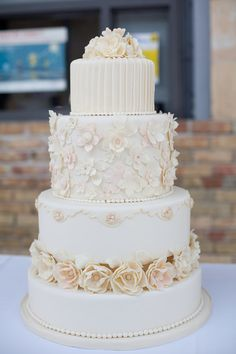 Flower adorned off-white four-layered cake