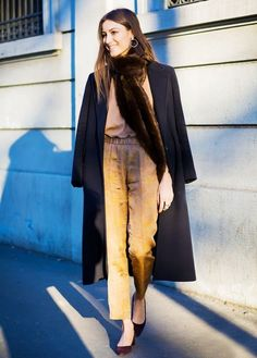 A neutral outfit is paired with a long black coat, fur scarf, and pointed-toe block-heel pumps