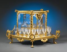 "This important Baccarat cavé liqueur was created in the same year Baccarat registered its first mark. Four etched Baccarat decanters and twelve matching cordial glasses are housed in their beautiful glass and doré bronze enclosure, which features an exotic dragon, bamboo and lotus blossom motif. Circa 1860  - 21 1/2"" wide x 13"" deep x 12 1/2"" high"