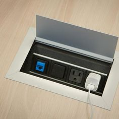 Hinged door power unit provides two electrical outlets and two open ports for data adapters. Steelcase