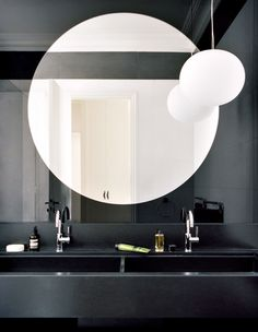 Dual Bathroom - one completly white wall and one is painted black. Looking in the mirror it comes together.