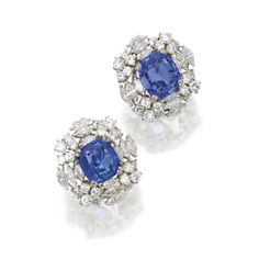PAIR OF SAPPHIRE AND DIAMOND CLUSTER EARCLIPS. Cushion-shaped sapphires together weighing approximately 9.00 carats, framed by marquise-shaped and round diamonds weighing a total of approximately 5.00 carats, mounted in white gold.
