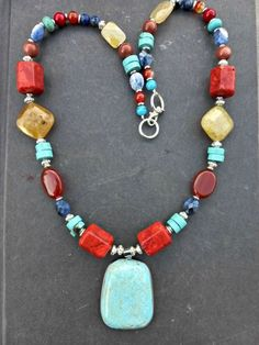 Blue turquoise stone pendant, red coral, orange agate, sunstone, blue lapis, yellow citrine and silver necklace.