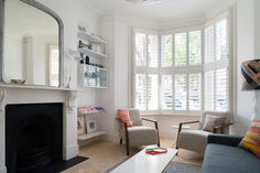 A traditional Victorian living room and bay window gets a modern makeover with white plantation shutters, perfect for light control and privacy. Shutters by The Shutter Store. Read more about the project here: http://shtst.re/1mYXzNP