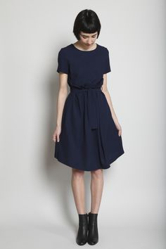 Navy high-twist gabardine dress with paper bag skirt overlay. Round neckline. Short sleeves. Self tie belt with side belt loops. On-seam side pockets. Hidden snap closure at back neck. Center back pleat detail. Dry clean.