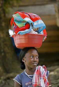 Suriname, Laduani, at the bank of the Suriname river. Woman from Saamaka tribe going to river to wash clothes.