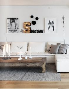 pictures, letters, marquee lights lean on a floating wall shelf. main colors of white + gray with rustic wood coffee table